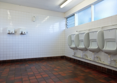 Empty public lavatory with urinals and hand dryers photo