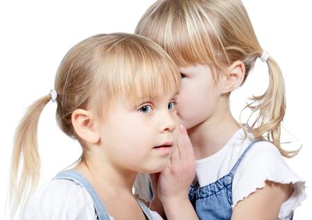 Portrait des kleinen Mädchens erzählt ein Geheimnis zu ihrer Freundin auf einem weißen Hintergrund