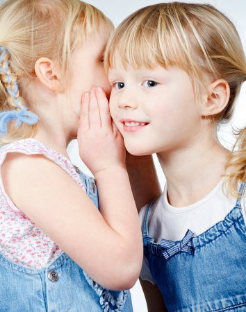 tattle: Portrait of little girl  telling a secret to her friend over a white background