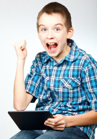 handheld device: Young boy pumps his fist and cheers holding a touch pad