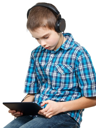 Portrait of 10 years boy wearing headphones using a touch pad photo