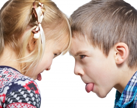 Sister and brother stick out tongues to each other photo