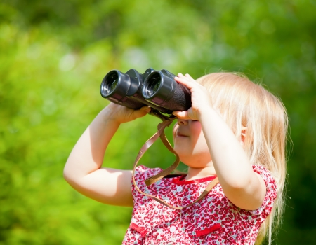 Little girl looking through binoculars outdoor photo
