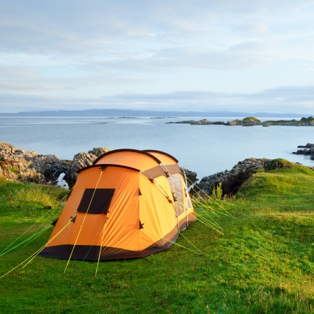 Camping tent on an ocean shore in a morning light photo