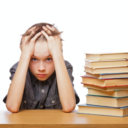 Portrait of upset schoolboy sitting at desk with books holding his head Фото со стока