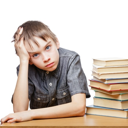 Portrait of upset schoolboy sitting at desk with books holding his head photo
