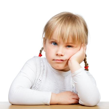 petite fille triste: Portrait de la malheureuse petite fille assise � son bureau avec la main sur le menton