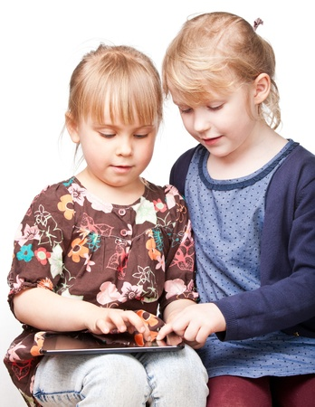 Two little girls using a touch pad photo