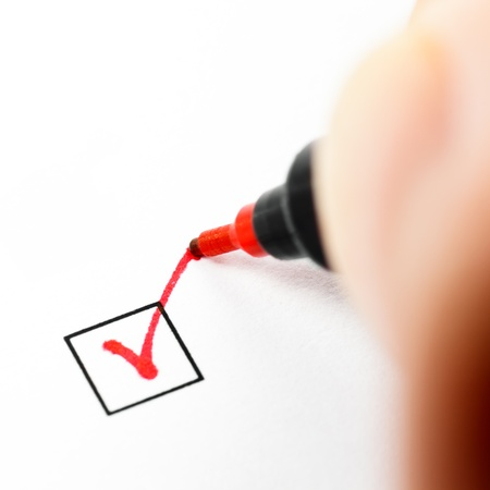 Hand with red pen marking a check box photo