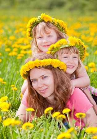 Young woman with two cute little girls enjoying a summer day outdoors photo