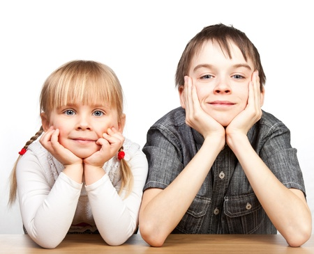 Portrait of cute girl and boy sitting at desk with hands on chin photo