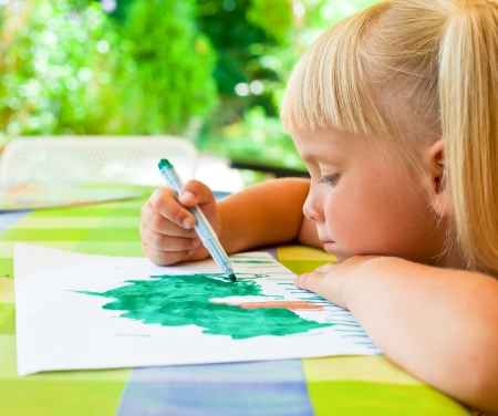 Cute 4 year old girl sitting at table drawing photo