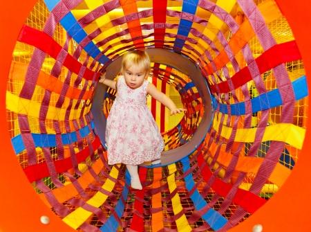 Spelen van het meisje in een tunnel van doolhof speeltuin Stockfoto