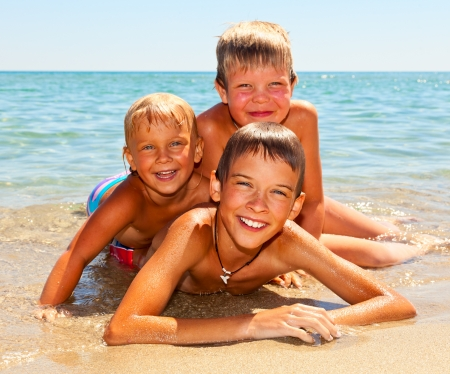 Three kids enjoying summer day on a beach Standard-Bild