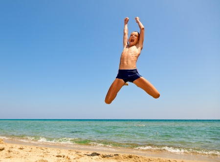 Kid jumping on the beach photo
