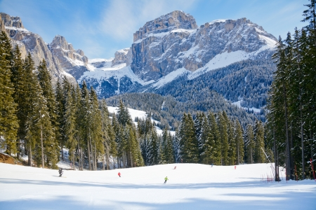 Skiers going down the slope at Sella Ronda ski route in Italy
