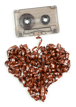 90s: Vintage transparent Compact Cassette with pulled out tape in the shape of heart on white background Stock Photo