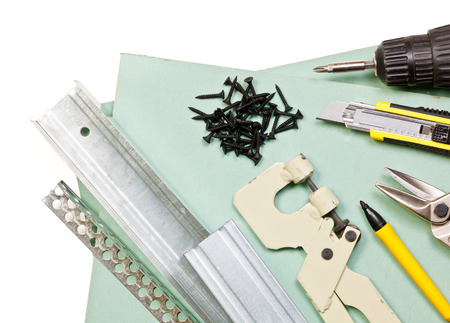 Plasterboard tools set with metal studs, screws, screwgun, cutter, punch lock crimper and tin snip cutter on white background photo