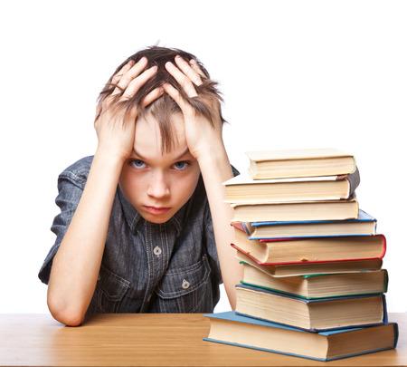 Portret van overstuur scholier zit op bureau met boeken die zijn hoofd