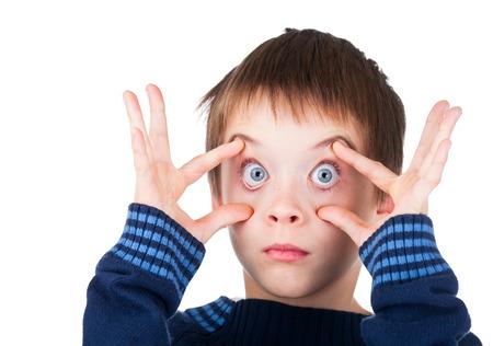 Kind gekleed in een blauwe trui die grappig gezicht met zijn ogen wijd open op een witte achtergrond