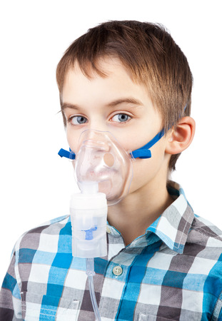 11 years: Portrait of cute boy using nebulizer on white background