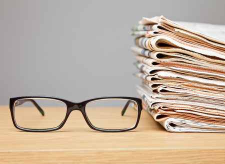 News concept Glasses on a table with stack of newspapers photo