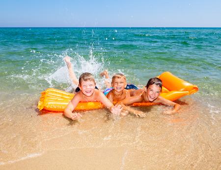Three kids splashing water on a beach photo