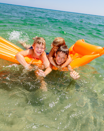 Three kids enjoying summer day floating in the sea photo