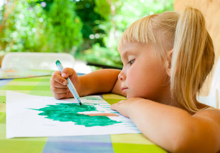 Cute 4 year old girl sitting at table drawing a tree photo