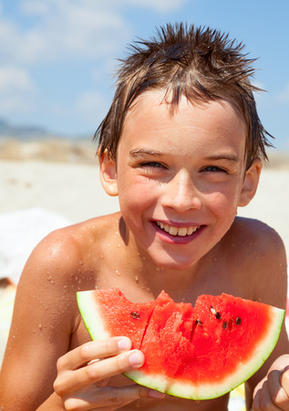 Happy boy eating watermelon on a beach photo