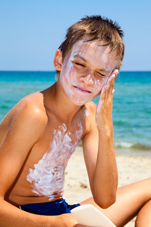 Child apply too much of sunblock cream photo
