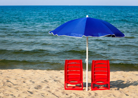 waterside: Two red plastic chairs with umbrella on a beach