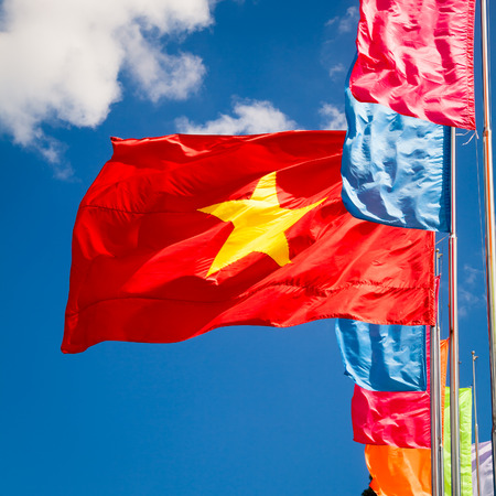 nam: Vietnamese flag waving in the wind against blue sky Stock Photo