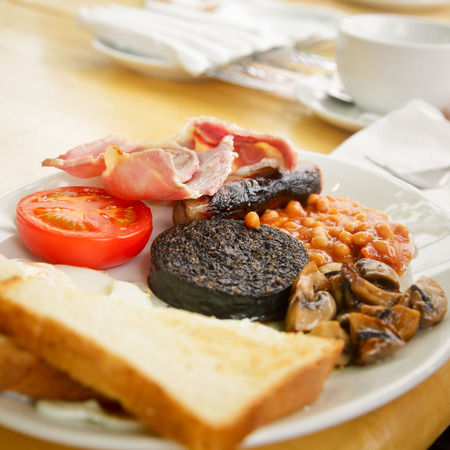 scottish: Plate with Full Scottish breakfast containing  toasts, fried eggs, baked beans, grilled black pudding, sausage, tomato,  mushrooms and bacon Stock Photo