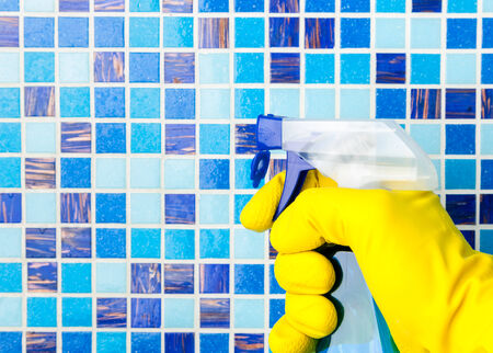 Hand in yellow protective glove holding spray bottle cleaning mosaic wall photo