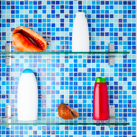 Bathroom shelves with shampoo bottles and seashells photo