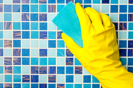 Hand in yellow protective glove cleaning mosaic wall with sponge photo