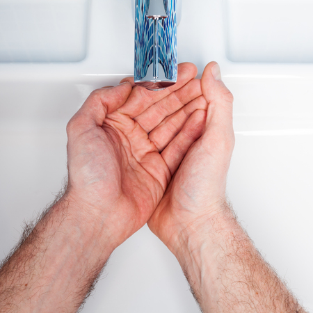 Man waiting to get water from bathroom sink photo