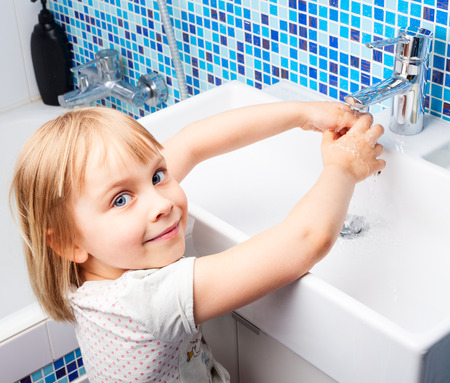 Little girl washing her hands in bathroom sink