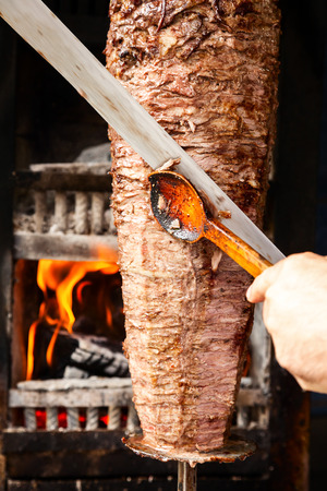 doner: Shawarma meat being cut before making a sandwich