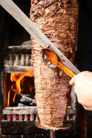 Shoarma vlees vóór het maken van een sandwich wordt gesneden Stockfoto