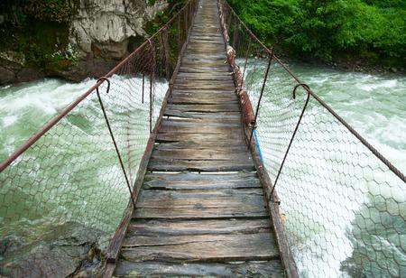 Rickety foot bridge over white water