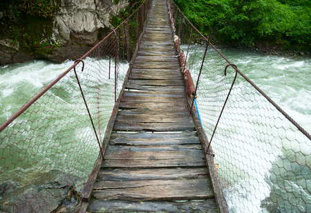 hanging on: Rickety foot bridge over white water