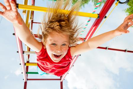 Little girl having fun playing on monkey bars Standard-Bild