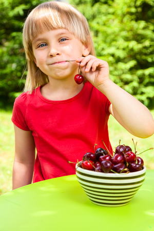 Cute little girl eating sweet cherry outdoors photo