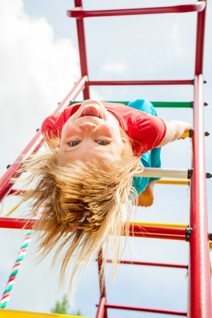 Little girl having fun playing on monkey bars photo