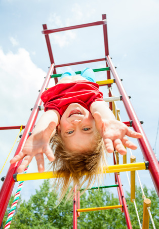 Little girl having fun playing on monkey bars photo