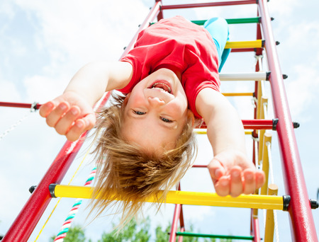 Little girl having fun playing on monkey bars Stock Photo