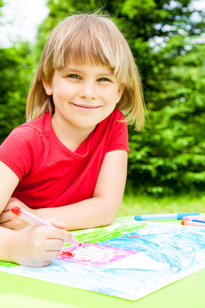 Little girl sitting at table drawing a house outdoors photo
