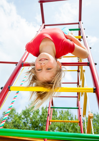 gripping bars: Little girl having fun playing on monkey bars Stock Photo